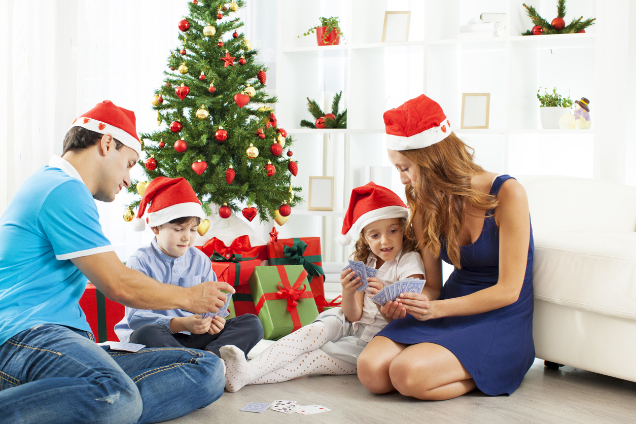 Portrait of a family with two children at home playing cards and having fun on Christmas