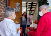 Happy senior couple arriving home for Christmas wearing facemasks and carrying presents while greeting to their kids