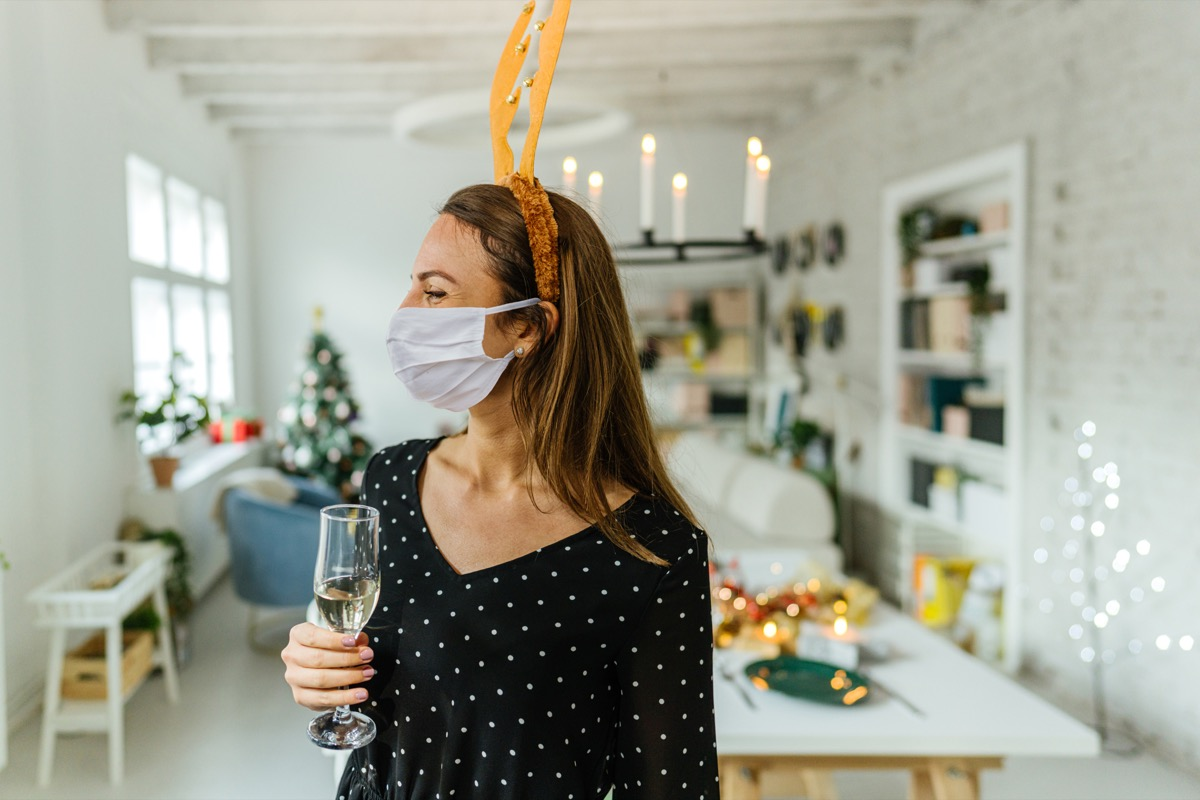 Photo of a young woman holding a glass of champagne, wearing a protective face mask and reindeer antlers; celebrating and hosting a Christmas dinner party at home during the COVID-19 pandemic.