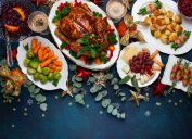 table with plates of brussels sprouts and carrots, cooked turkey, scallops, and cheese on table with blue tablecloth and eucalyptus leaves