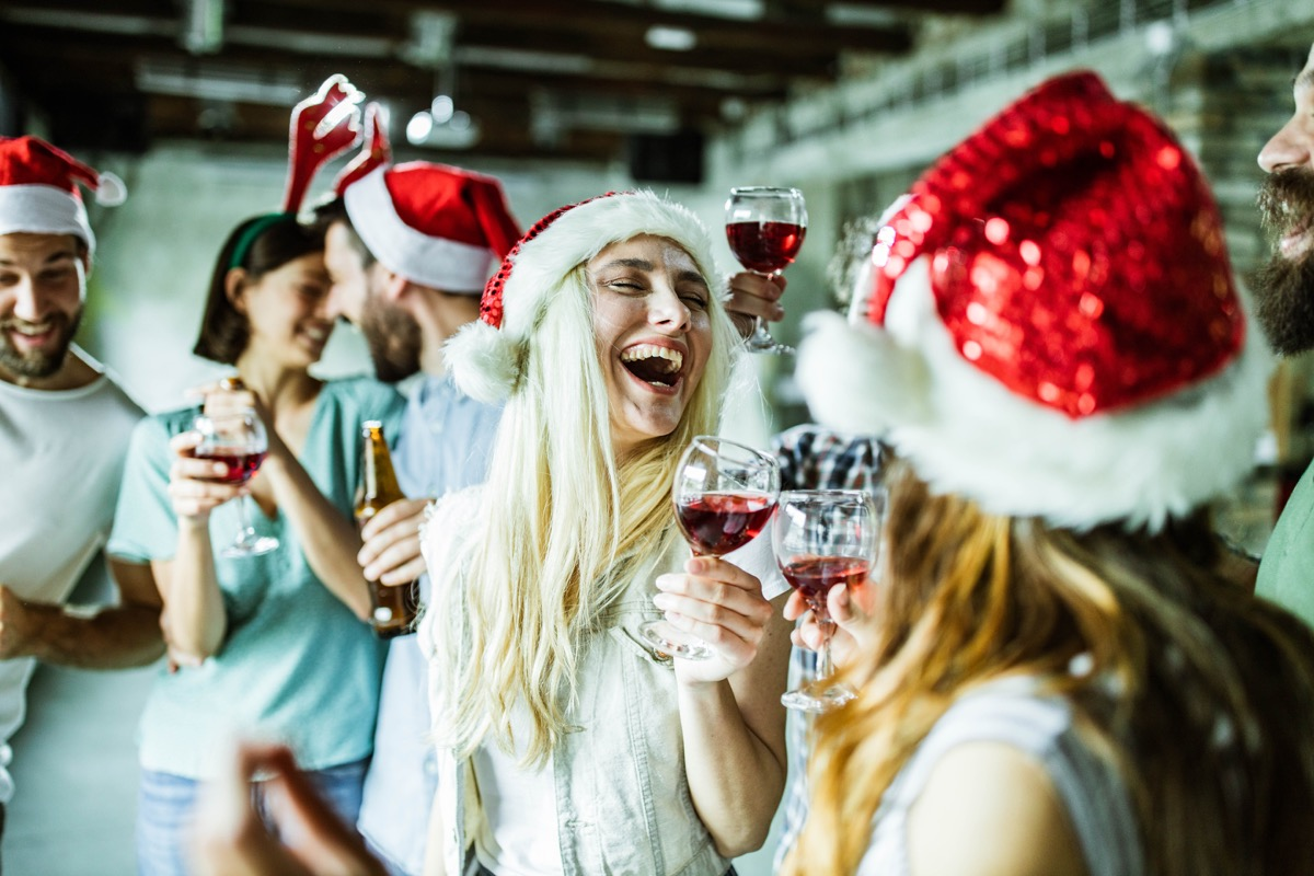 Group of cheerful creative people having fun on Christmas party in the office. Focus is on blond woman.
