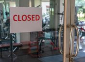 Closed sign on a glass of the door in gym due to Covid-19