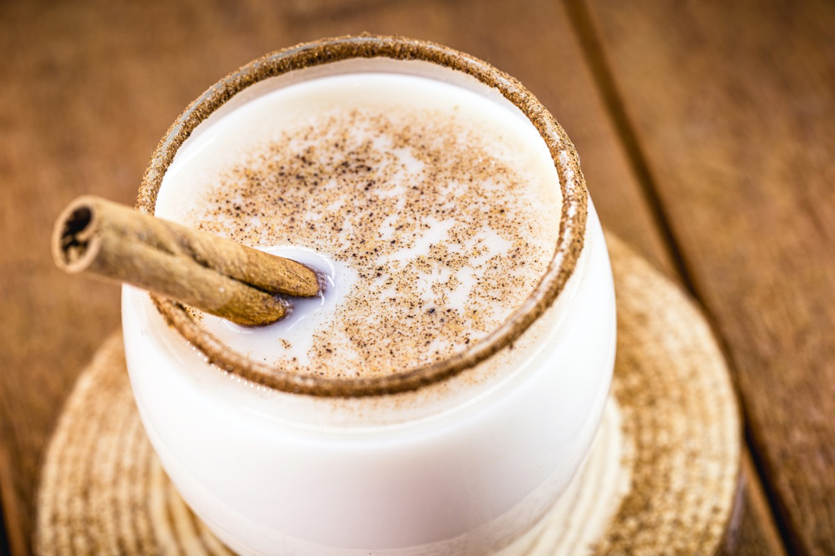 coquito or coconut eggnog in clear glass with cinnamon stick