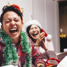 A happy young couple are sharing a good time with laughter on Christmas.