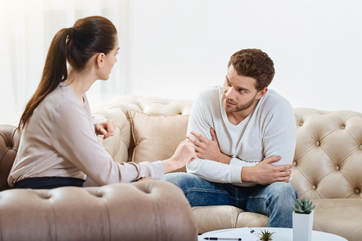 man looking at woman and woman towards to the man on a couch