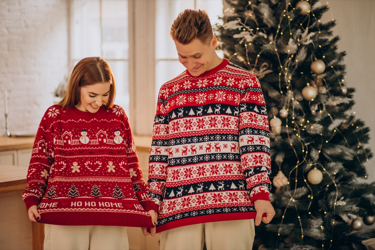 couple wearing Christmas sweaters in front of tree