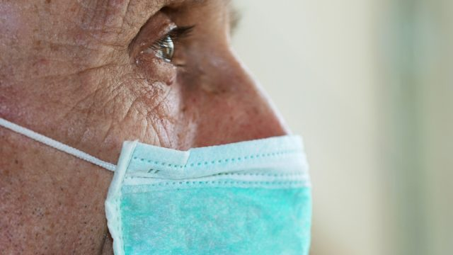 face of elderly man wearing medical facemask
