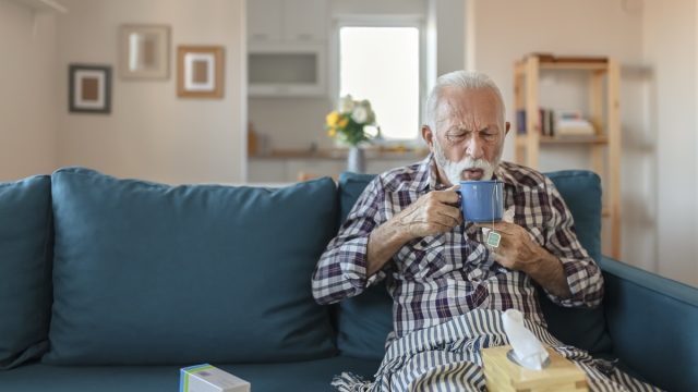 Senior man suffering from flu drinking tea while sitting wrapped in a blanket on the sofa at home. Sick older man with headache sitting under the blanket in the living room. Man with a cold lying on the sofa holding a mug of hot tea.