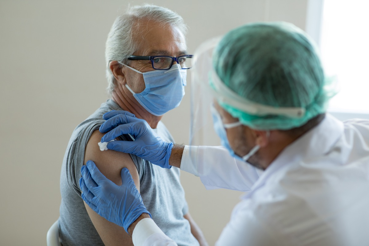 Doctor disinfecting patient's skin for vaccination