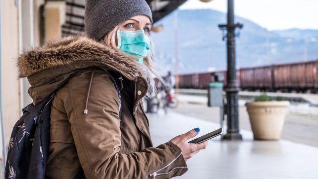 Woman wearing face mask while at train station in the winter during COVID