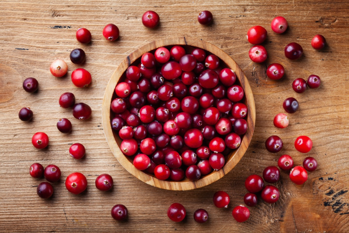 Cranberries in wooden bowl on wood surface