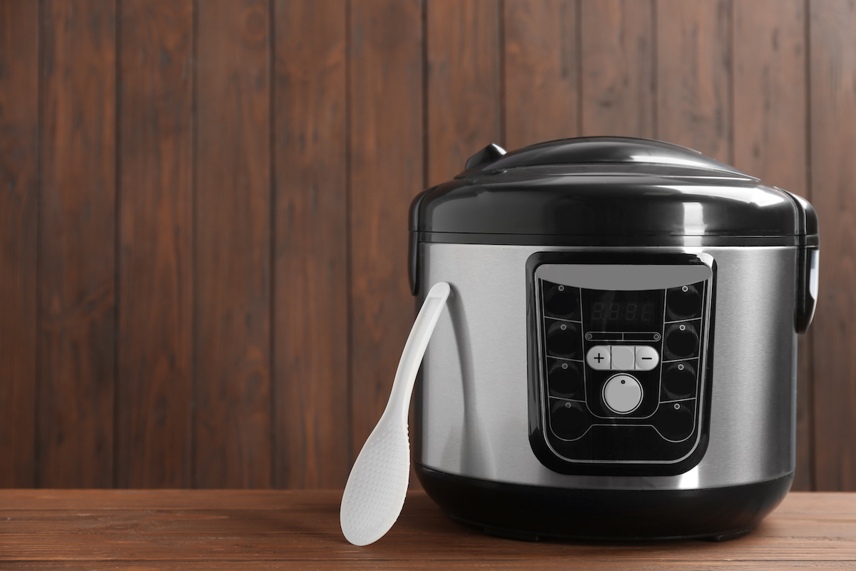 Modern powerful multi cooker on table against wooden background