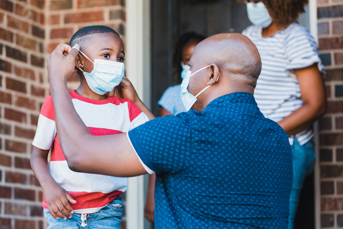Father helps son put on protective face mask