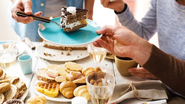 Man putting piece of chocolate cake on saucer of one of guests at party