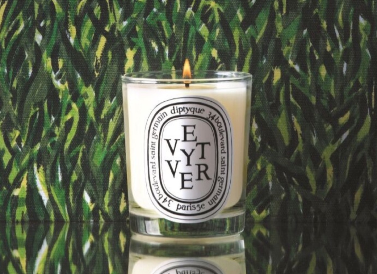 diptyque vetiver candle in front of green background