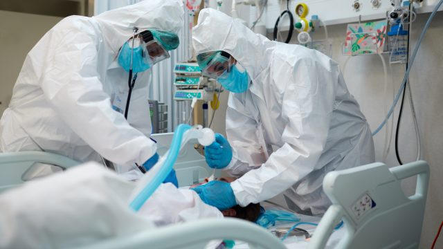 Two doctors wearing protective gear intubate a COVID patient in the ICU.