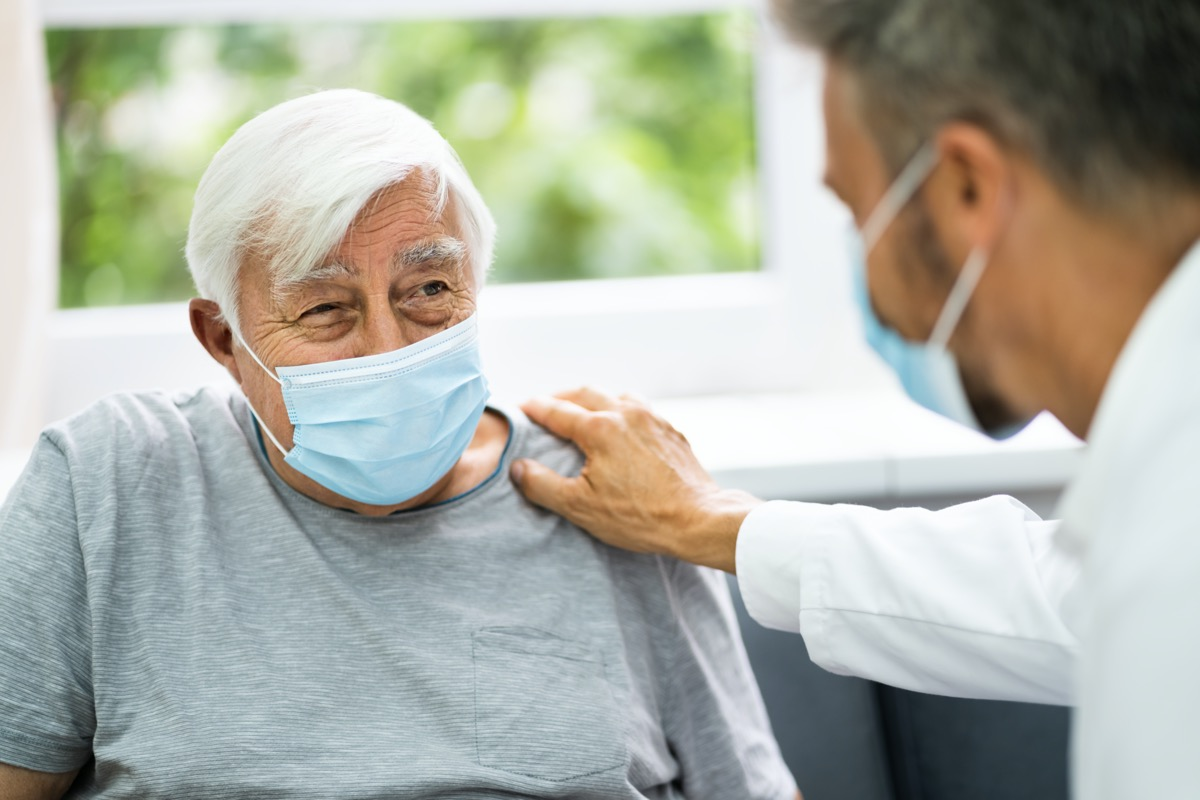 doctor talking to elderly patient wearing mask