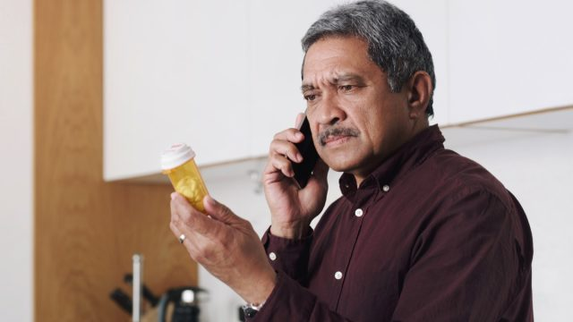 Shot of a senior man reading the label on a medicine container and talking on a cellphone