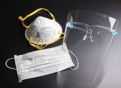 Face shield, surgical mask, and N95 mask on a black background