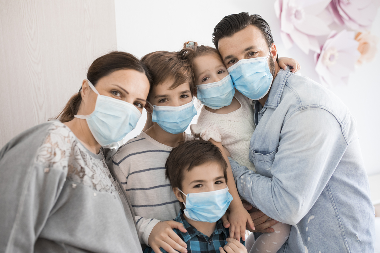 A family of a mother, father, and three children all wearing face masks while indoors.