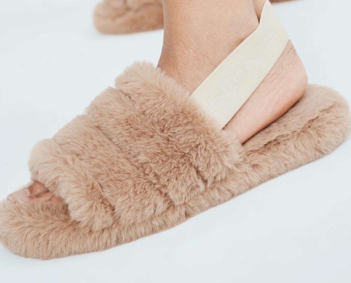 feet in brown faux fur slides