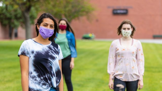 A group of three female friends wearing face masks while socially distanced outdoors.