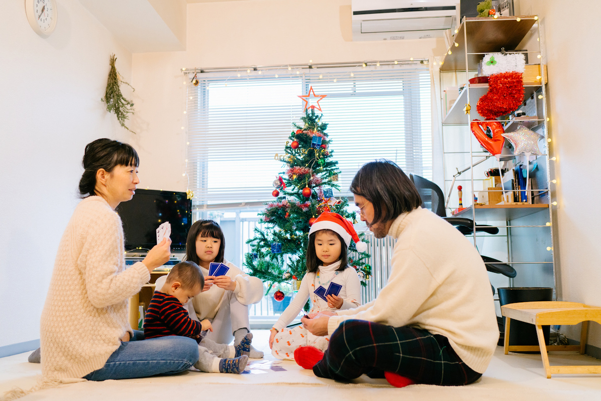 A family is sitting on floor and playing cards games in the living room decorated with Christmas ornaments and a Christmas tree during Christmas.