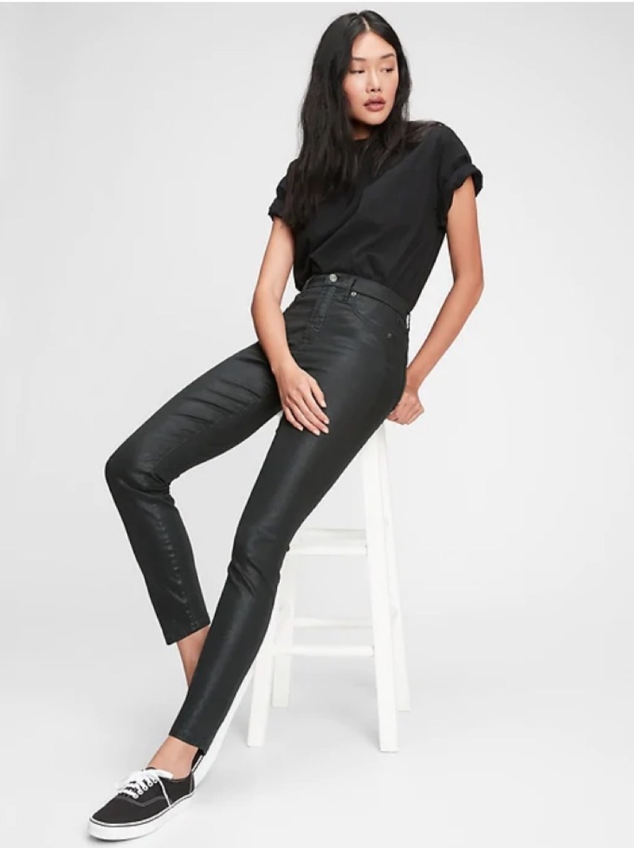 young woman sitting on stool wearing cropped jeans and black shirt
