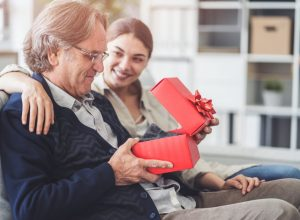 young girl giving father gift in red box