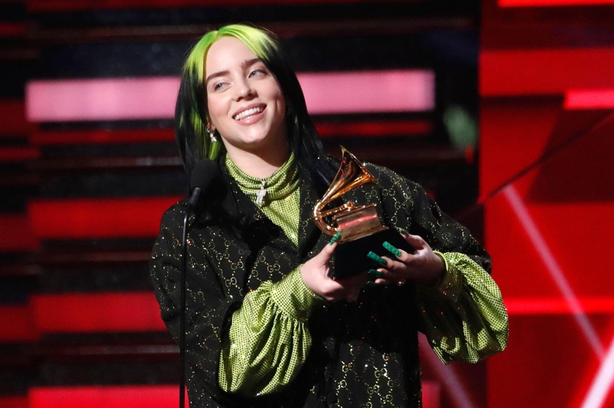 Billie Eilish holding up her Grammy at the awards show in 2020