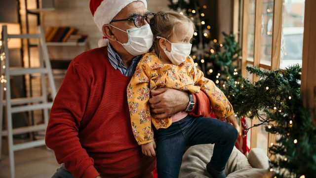 A grandfather wearing a face mask Santa hat hugs his grandaughter from behind during a holiday celebration.