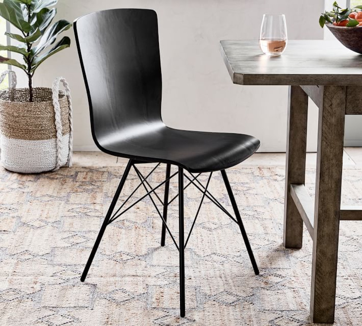 black dining room chair next to wooden table and plant in two-toned pot