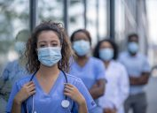 A group of doctors and nurses wearing face masks stand socially distanced while outside.