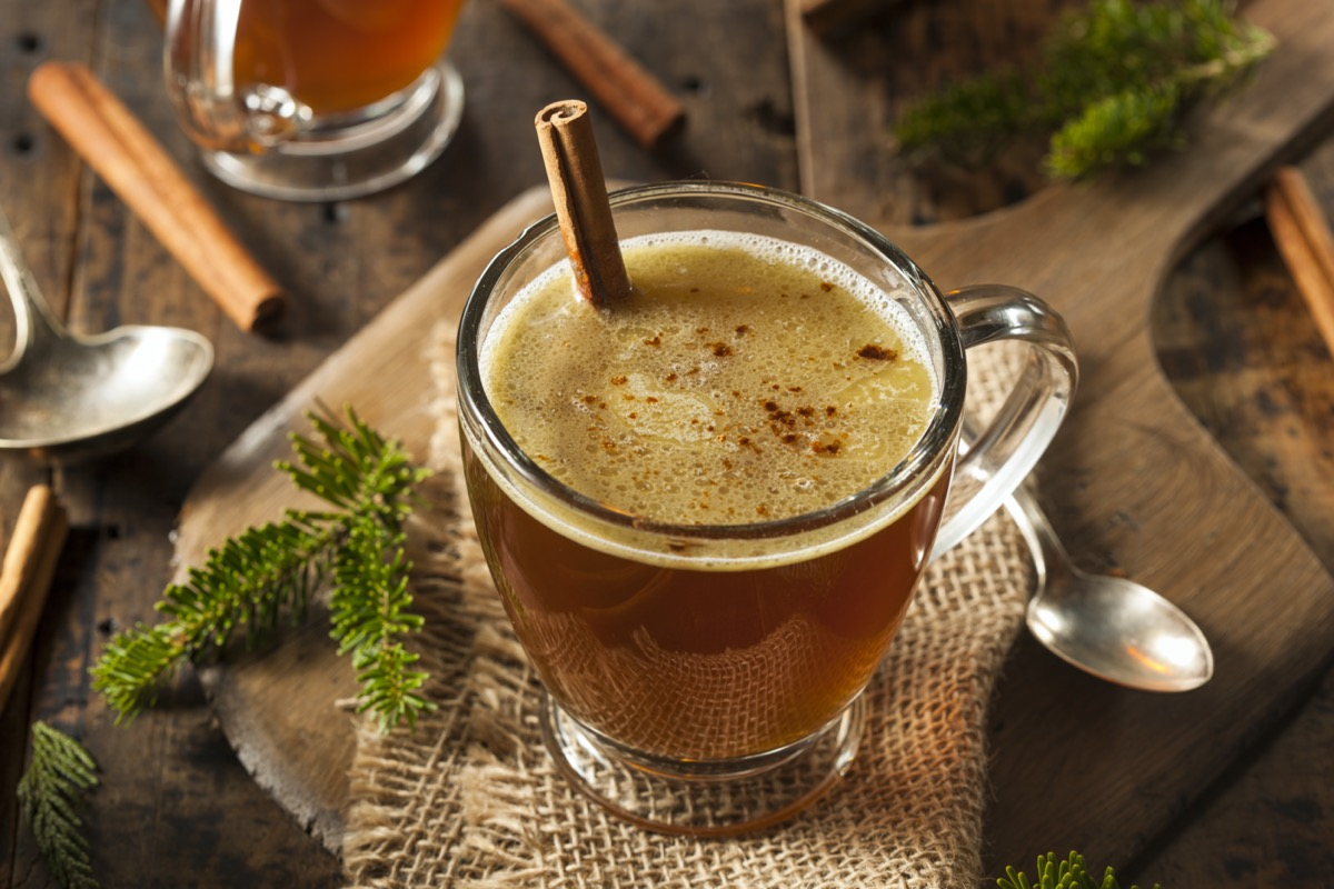 hot buttered rum in mug with cinnamon stick in clear mug