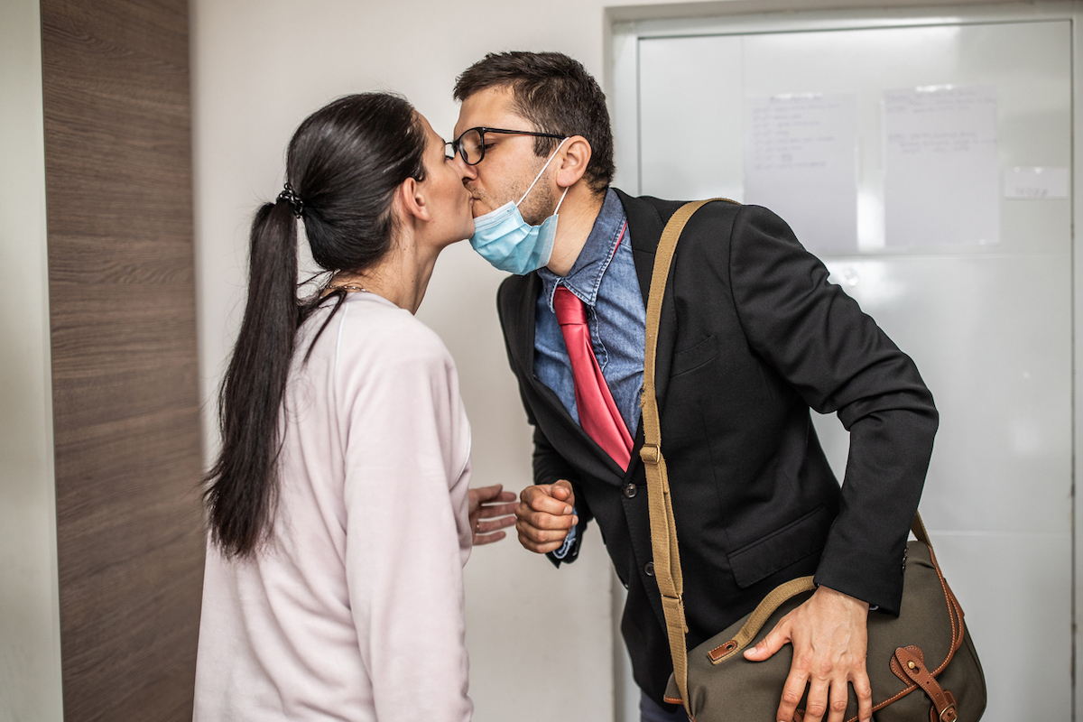 Husband arrives home after work with mask on chin