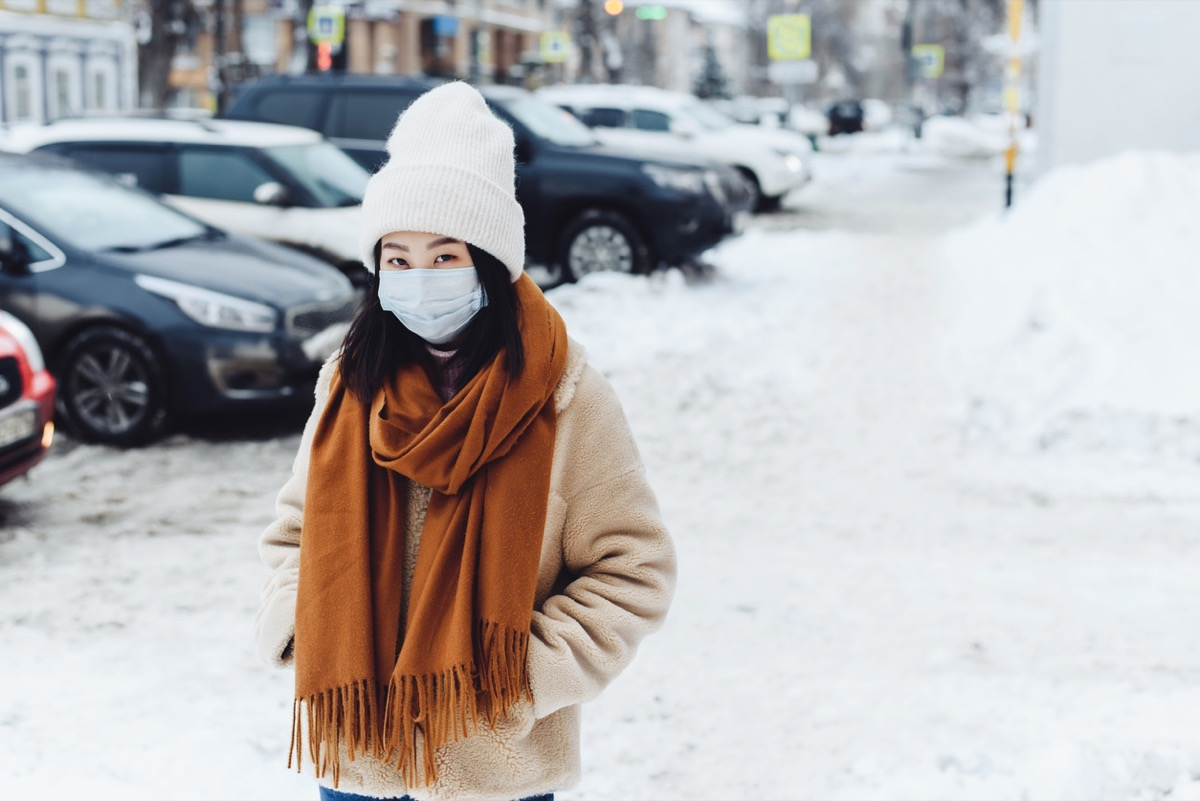 woman wearing face mask and winter clothing outside in the snow