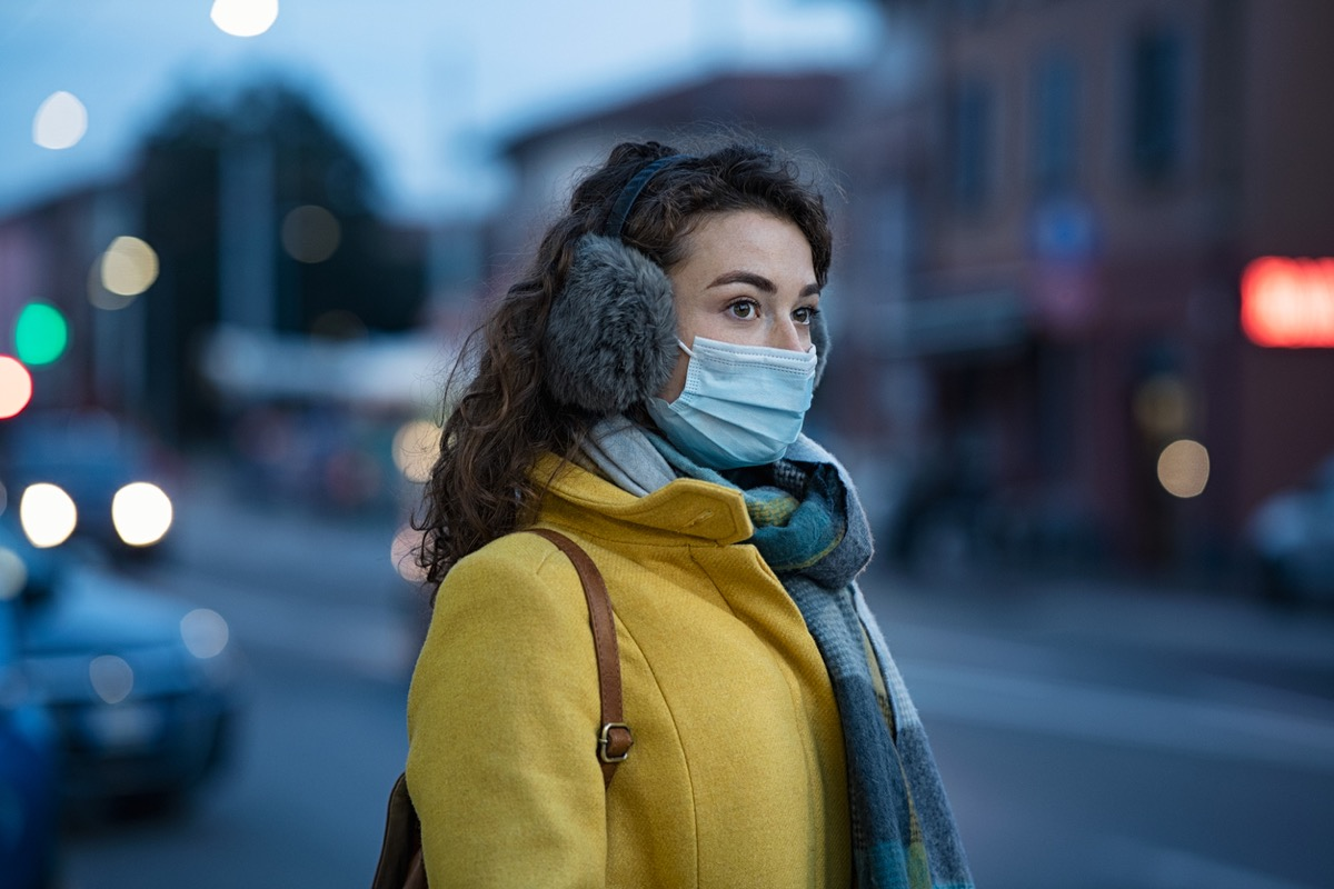 woman with a face mask and ear muffs standing outside in the winter