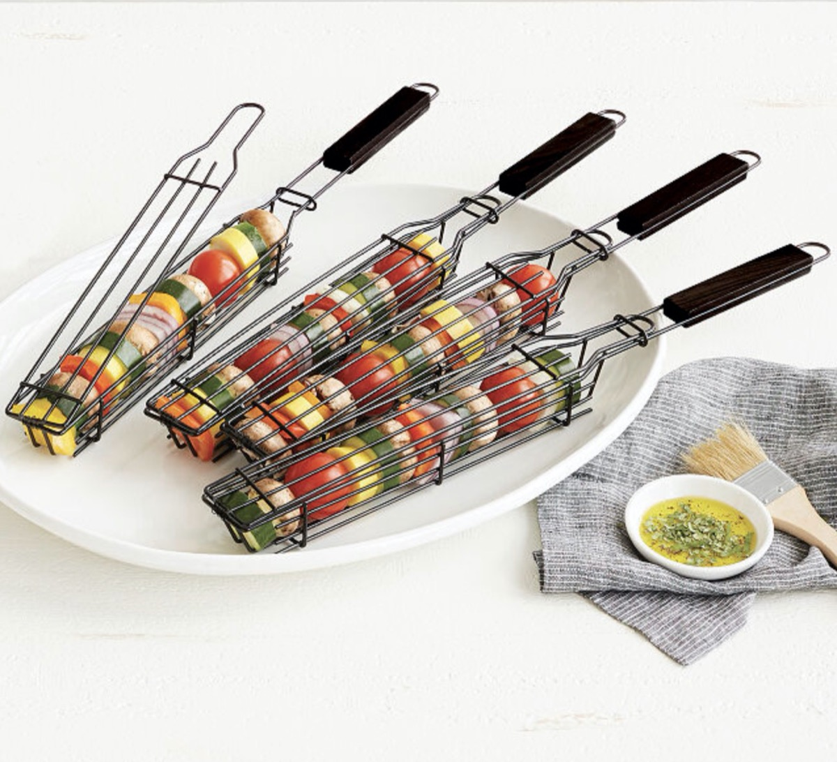 kabob grilling baskets on white plate next to small dish of oil