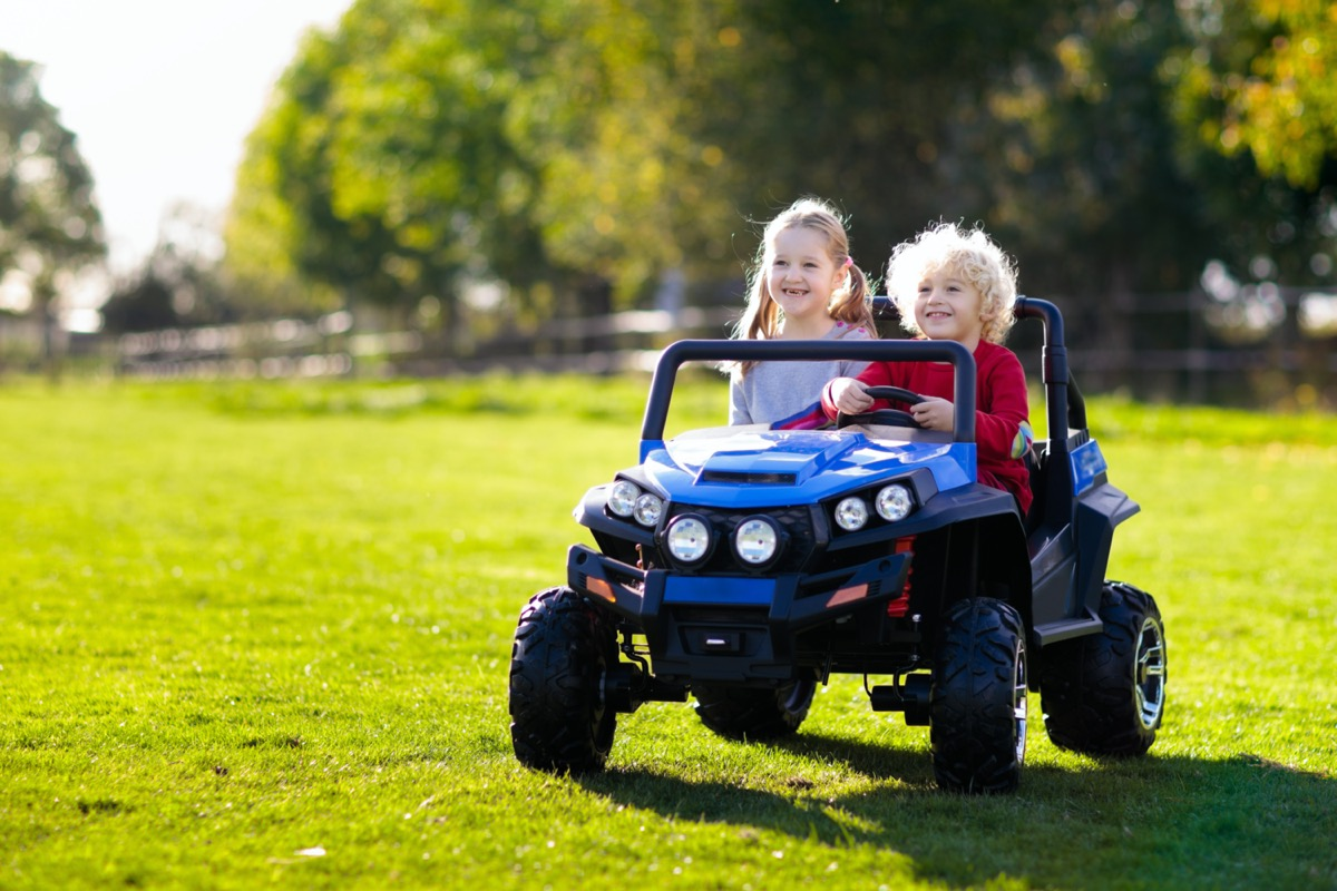 two little kids riding in ride on toy or utv