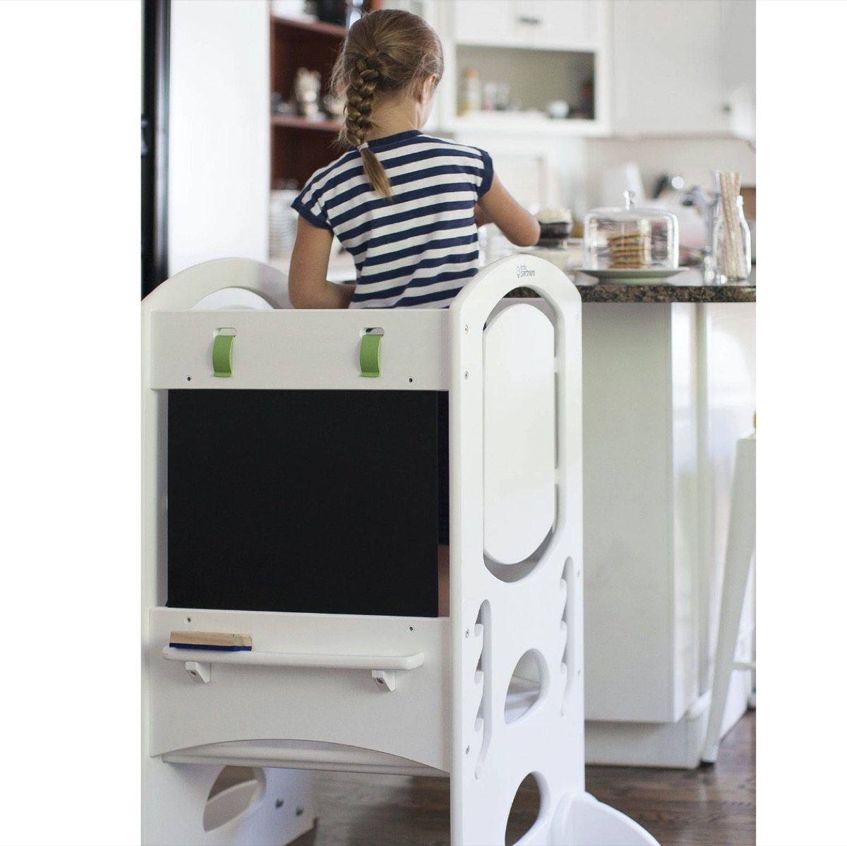 child cooking on white step ladder