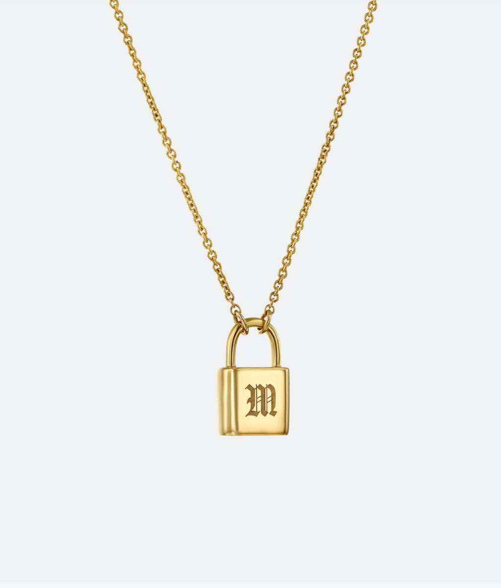 gold necklace with lock bearing the letter M on it