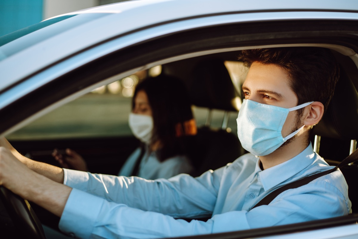 Man driving a car puts on a medical mask during an epidemic in quarantine city. Health protection, safety and pandemic concept. Covid- 19.