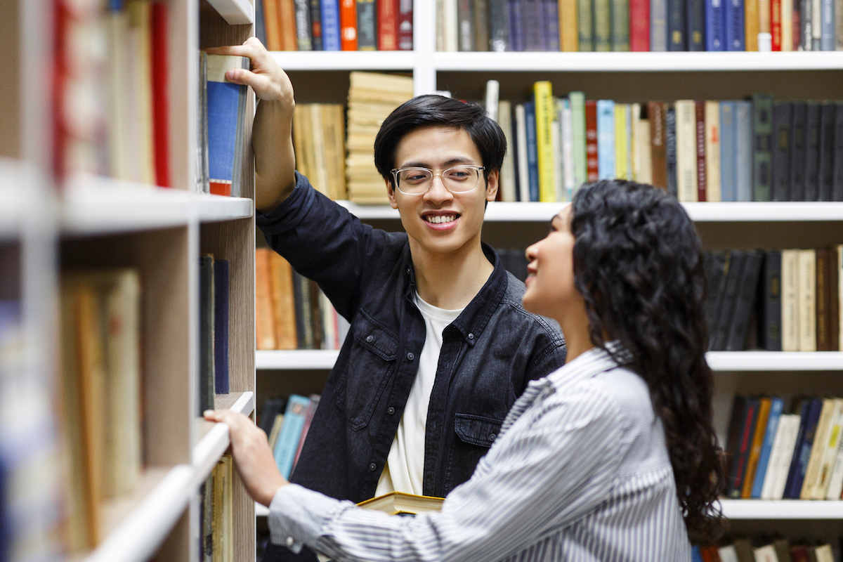young man in glasses taking book from library bookshelf in campus library while smiling at girl