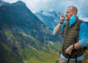 asthmatic man enjoying some fresh air outdoors in the Alpine mountains while wearing covid mask