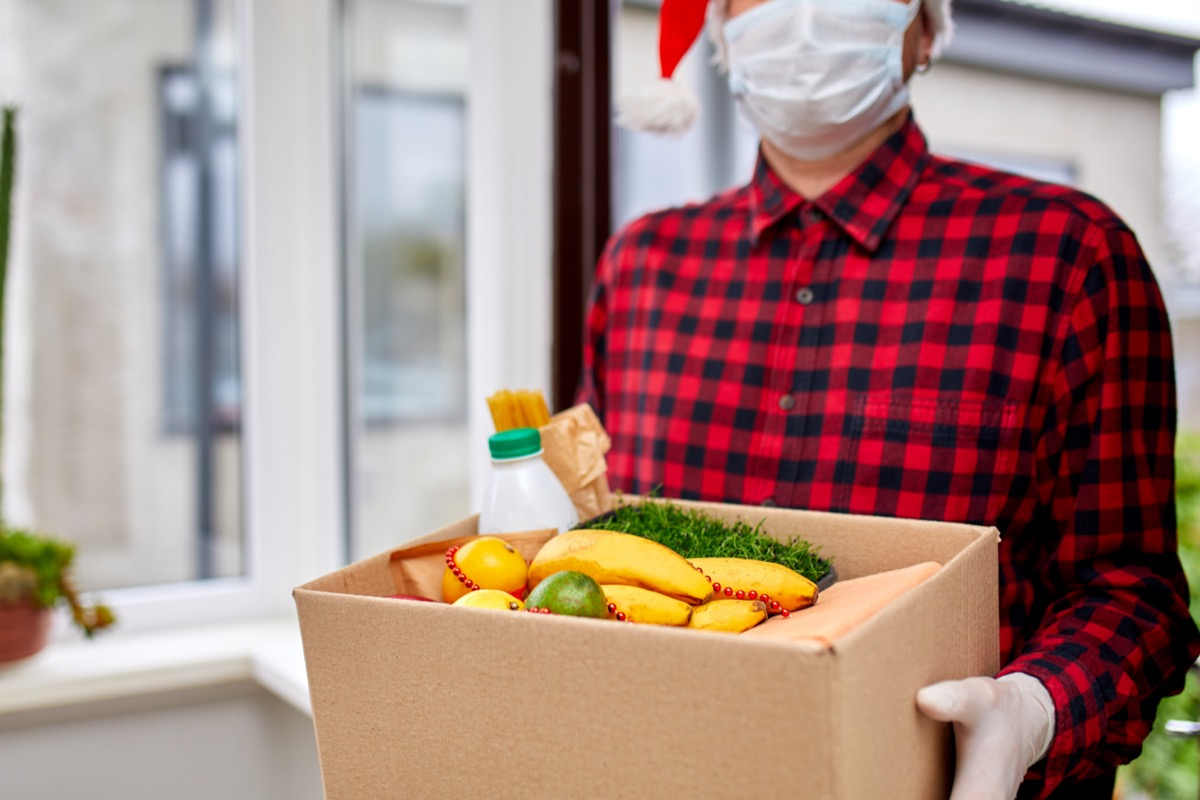 A man holding a box with food while wearing a mask and Santa hat