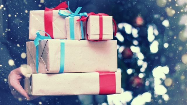 man standing outside holding holiday gifts wrapped in brown paper with colorful bows