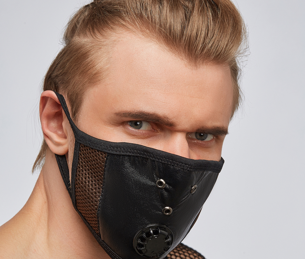 Close-up portrait of a blond man, wearing a black leather mask with brown mesh under it and ventilation openings.