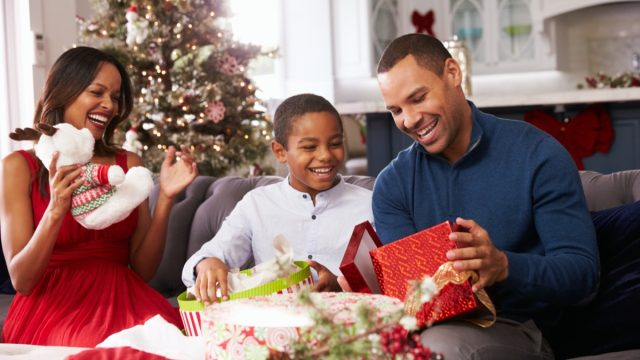 man opening presents with family