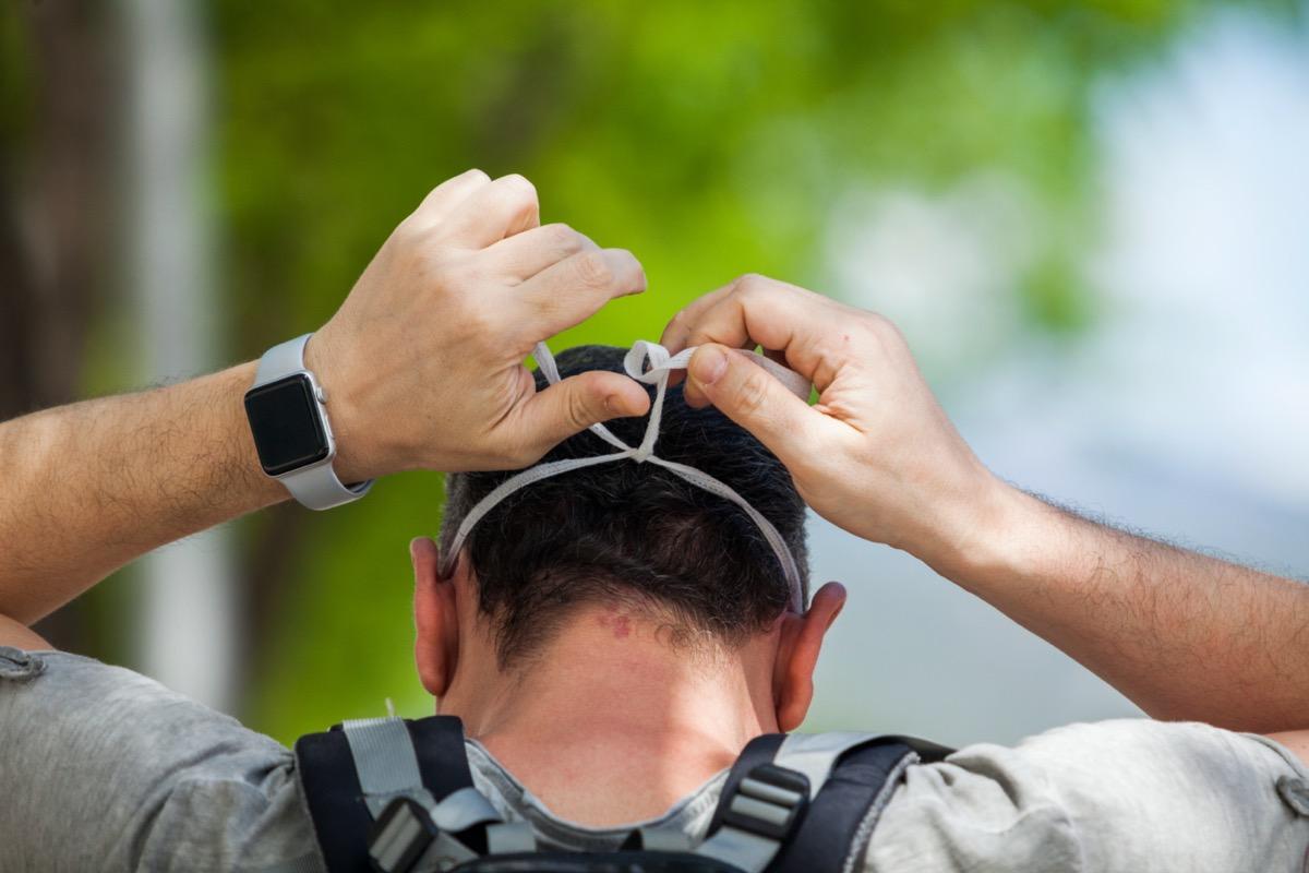 man tying on face mask