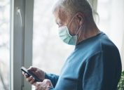 Senior man wearing a protective mask and using a phone at home, during COVID-19 pandemic.